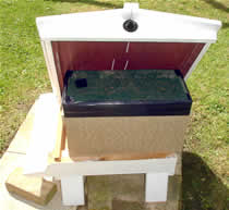 Travelling box placed on stand and shielded from the sun and wind